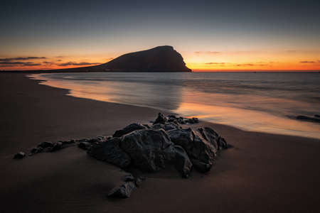 landscape of a sandy beach in a sunset and with reflections in the water