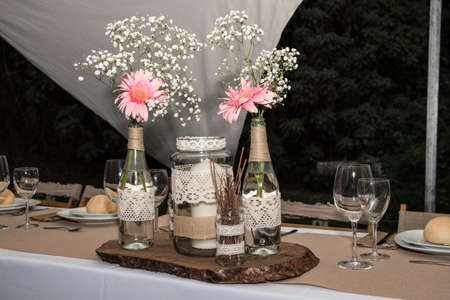 pretty set of bottle and flower vases adorning a table