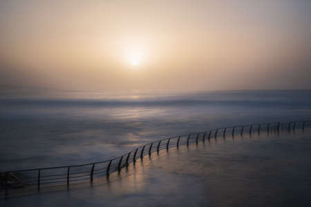 you can see a sunset with a natural pool in the sea smooth lines long exposure Фото со стока