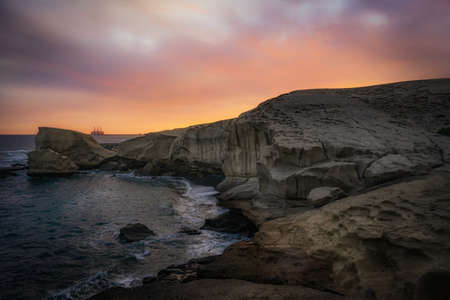 sunset where you can see mountains and the sea warm colors