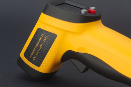 infrared: Infrared thermometer in black background Stock Photo