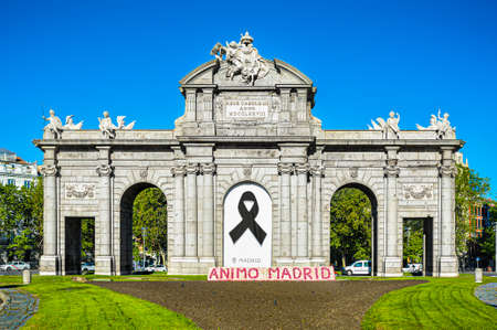 MADRID, SPAIN - MAY 18, 2020: The Puerta de Alcala (Alcala Gate) on the Plaza de la Independencia (Independence Square) in Madrid, Spain, during the coronavirus pandemic. A black ribbon as a mourning