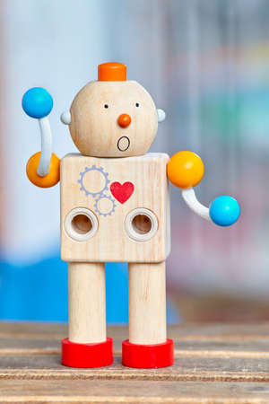 Wooden toy robot with red heart and surprise face. Defocused background. Stock Photo