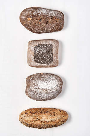 From above shot of healthy heavy loaves of bread composed in line on white surface.
