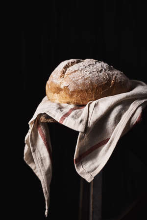 Composed loaf topped with flour on rustic kitchen towel with black background. Stockfoto