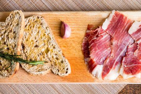 aperitive: Spanish iberico ham with toasts on wood table Stock Photo