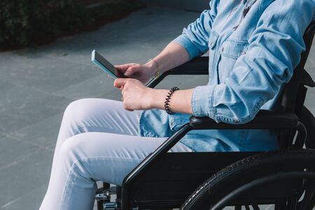 Disabled girl in a wheelchair using her mobile phone.Disable and technology concept