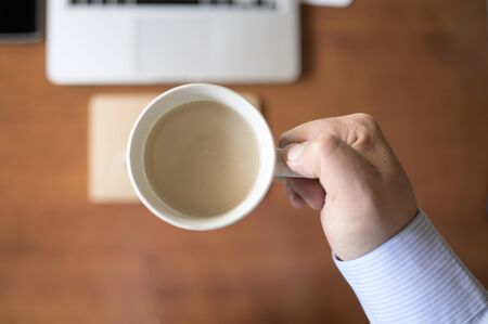 Businessmans hand holding a cup of coffee in office desk .Wooden desk with laptop and notebook on an unfocused background.Business and work concept