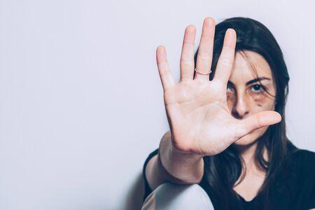 ジェンダー暴力に対する停止の概念。虐待を受けた白人女性が床に座り、白い壁に寄りかかっていると、腕が伸びていて、手のひらが開いて停止するジェスチャーをします。彼女の顔は怪我や打撲傷を示しています。スペースをコピーする