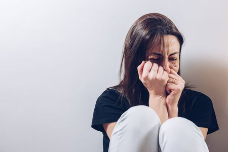 Attractive young woman, takes her clenched fists to her injured face to cover herself while she cries. Concept of abuse and health.