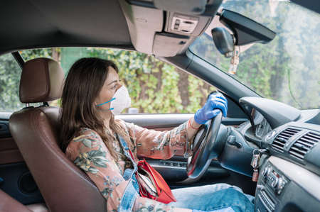 View of the inside of a car of a young girl with a flu mask and sanitary gloves. Health care and mobility concept 스톡 콘텐츠
