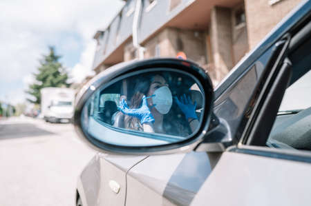 View of the rear view mirror of a car in which an attractive woman wearing medical gloves is seen putting on a flu mask.Copy space.Selective focus.Healthcare concept, Covid-19