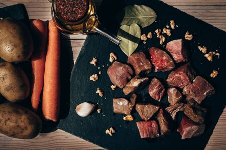 Top view of raw beef cut into a black slate plate with bay leaves and garlic, surrounded by olive oil, carrots and potatoes on a rustic wooden table. Concept of food and life healthy.