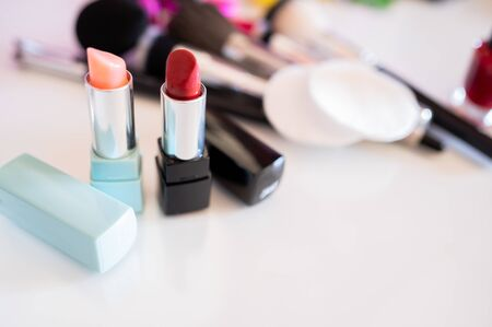 Lipstick in different colors next to cosmetic products. Concept of feminine beauty and personal image care.