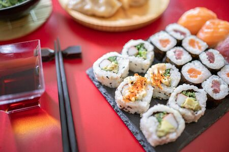 Set of sushi.Sushi rolls set with tuna and salmon fish, soya sauce ,wakame salad isolated on red background.