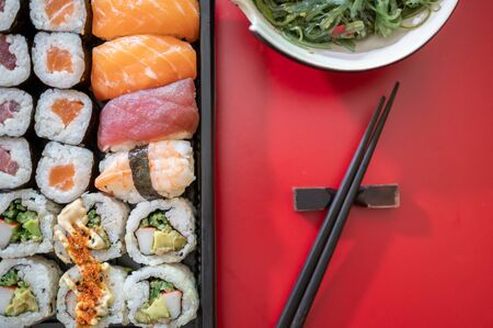 Delicious japanese food isolated on red background.Delivery service.Top view.