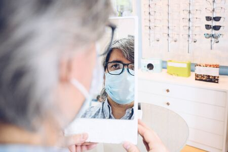 Gray-haired man wearing a covid mask19 in front of a small mirror in an eyewear store