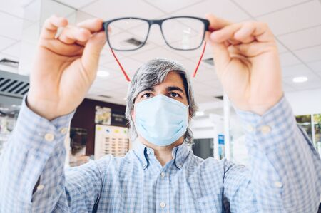 Middle-aged man wearing flu mask holding modern glasses in his hands . Selective focus.Copy space 스톡 콘텐츠