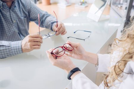 Blonde optometrist girl shows different models of glasses to a client.