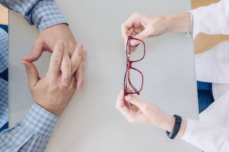 Top view of optometrist girl and client holding glasses at eye clinic