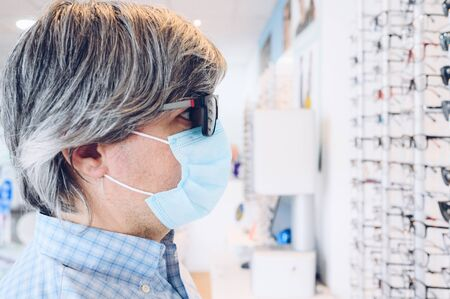 Man with flu mask wearing sunglasses at an eyewear store. Business, shopping and eye care concept 스톡 콘텐츠