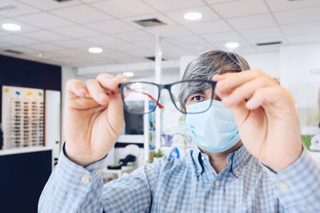 Middle-aged man wearing sanitary mask holding elegant glasses in his hands at an optician's. Selective focus.Copy space