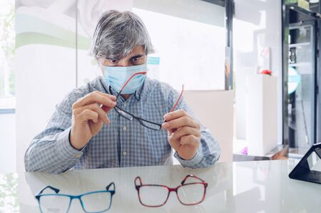Man in a flu mask holding a pair of glasses in an eyewear store. Concept of eye care