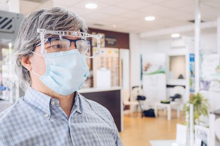 Caucasian man with grey hair wearing a sanitary mask, balancing his new glasses in an eyewear store