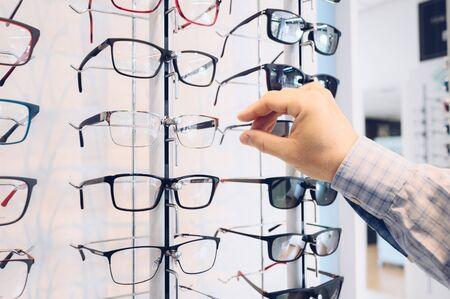 Choosing glasses in a eyewear store 스톡 콘텐츠