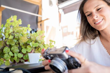 Pretty and happy girl checks photos of her vacations on her vintage camera in a coffee shop Stock Photo
