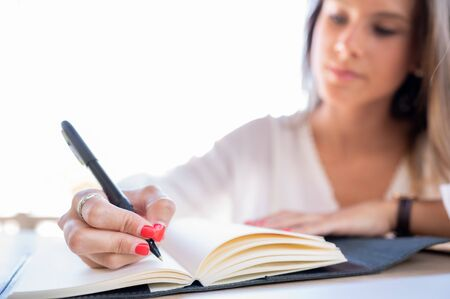 Attractive young woman writes down a business idea in her notebook