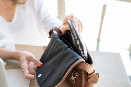 Woman takes out her purse for the money to pay. Concept of business and payments