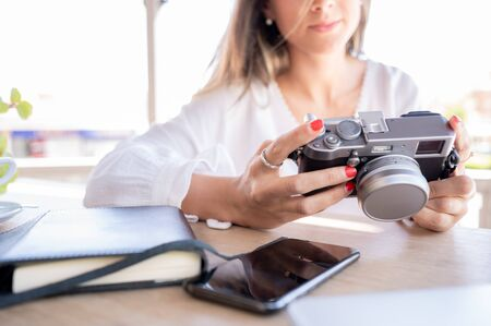 Pretty and successful blogger girl checks photos on her vintage camera.