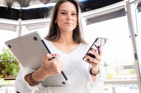 Happy young girl looking at camera while holding her cell phone and laptop. Lifestyle. Concept of beautiful and active people.