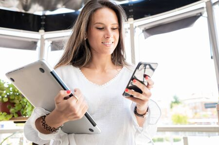 Elegant and stylish young girl looks happily at her smart phone while holding a laptop in her other hand. Office anywhere. Concept of work, beautiful people 스톡 콘텐츠