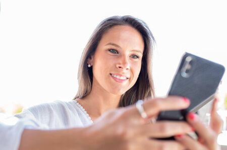 Young entrepreneur girl looks happily at her smart phone 스톡 콘텐츠