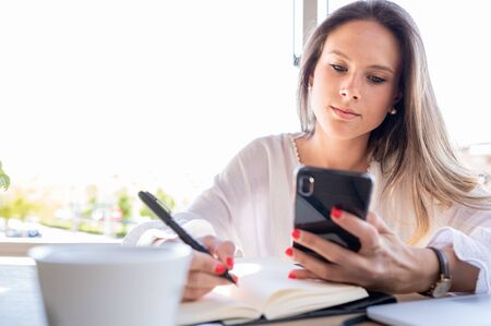Beautiful young girl, successful entrepreneur looking at her mobile phone and writing in her notebook. Copy space. Business and young entrepreneurs concept