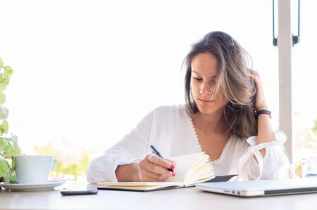 Young entrepreneur writes down in her notebook new ideas for her small business. On the table a cup of coffee, a smart phone and a laptop.Copy space 스톡 콘텐츠