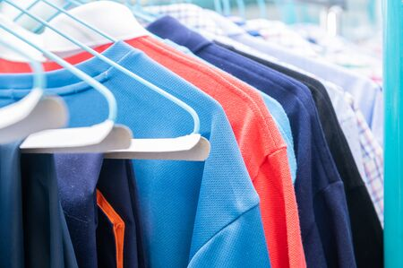 Clean, brightly colored sweaters hung on hangers in a dry cleaner's