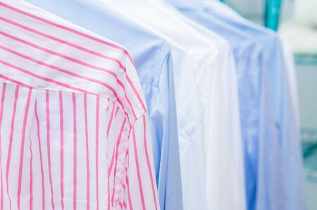 Clean shirts hung on hangers. Different colors.