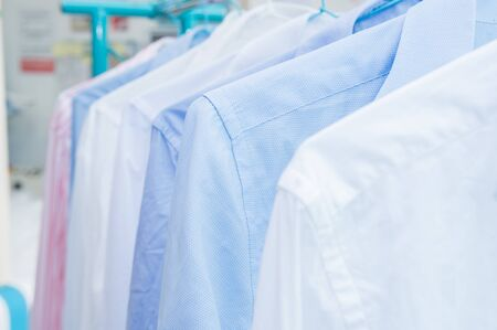 Rack with clean shirts on hangers after dry-cleaning indoors 스톡 콘텐츠