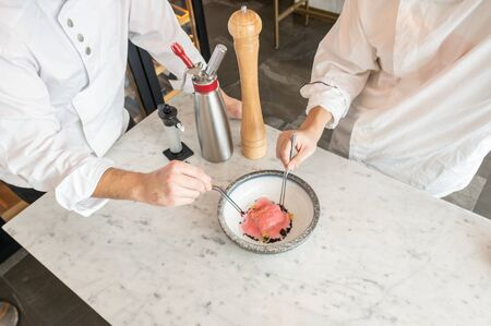 two professional chefs place the last ingredients on a delicious and colorful plate of food in a restaurant 스톡 콘텐츠