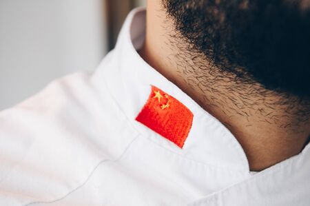 Chef with a beard wearing a work jacket with the Chinese flag 스톡 콘텐츠