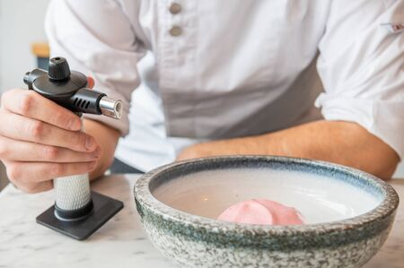 Professional chef holding a kitchen torch to be used in one of his creations 스톡 콘텐츠