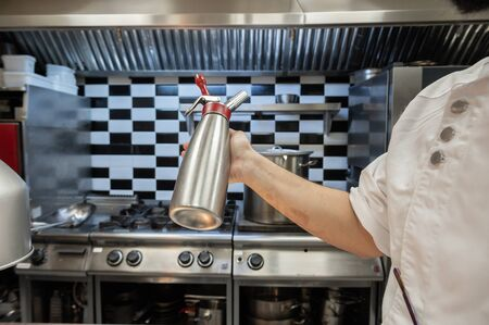 Professional chef holding a foam siphon in a restaurant kitchen