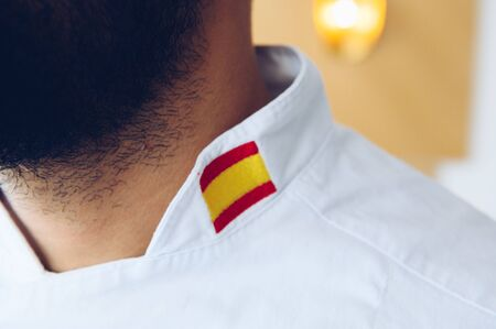 Chef with a beard wearing a work jacket with the Spanish flag