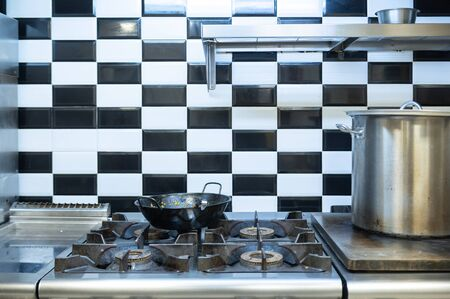 Stylish restaurant kitchen with a frying pan on the stove. 스톡 콘텐츠