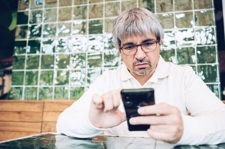 Middle aged man sitting in a bar using smart phone.People and technology concept 스톡 콘텐츠