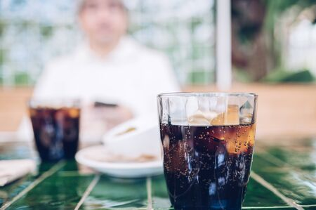 Glass of drink of cola on a table in a restaurant during a working lunch