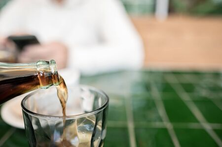 Pouring cola into a glass at a friend's meeting. Selective focus. In an unfocused background, a man holding a cell phone.Copy space